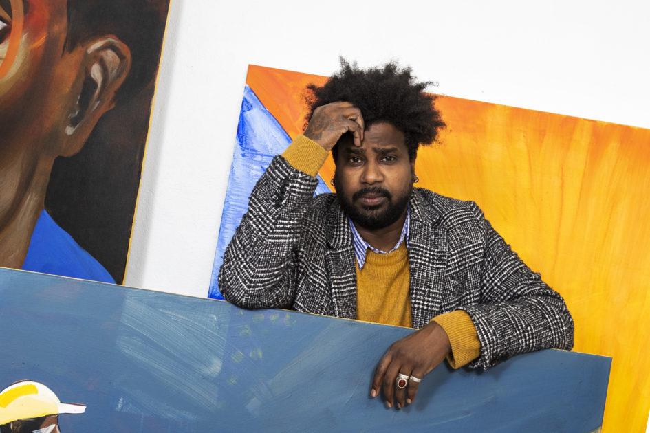 Kunstneren Fadlabi i sitt studio, omgitt av malerier i sterke farger.